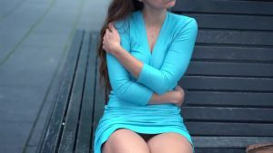 A girl in a blue dress shows her right tit and that she is without panties